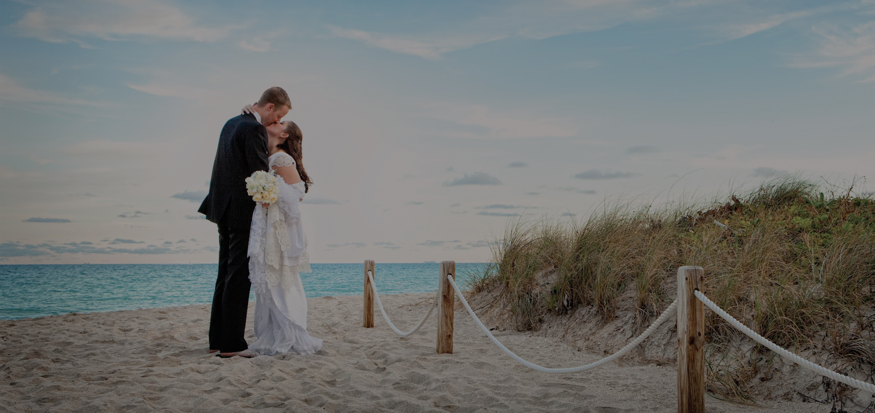 Wedding couple kissing at the beach in front of the Deauville Beach Resort