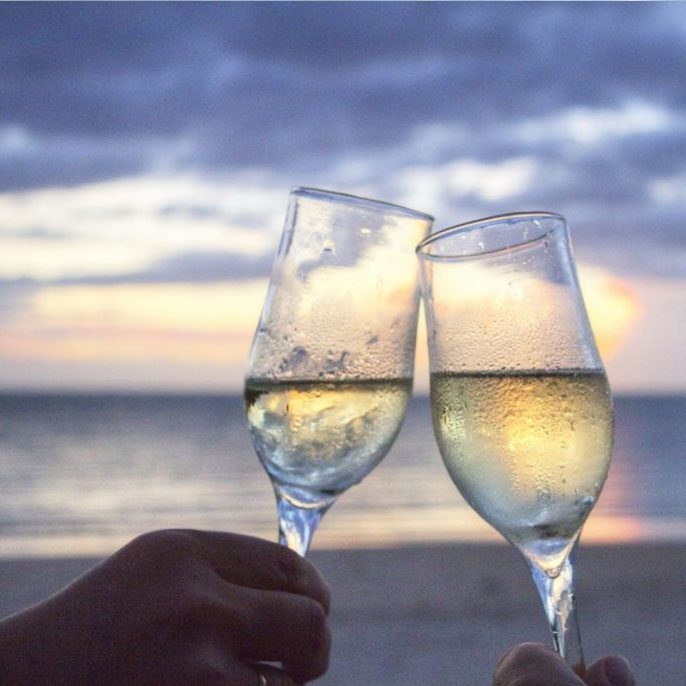 Wine toast at sunrise at the beach