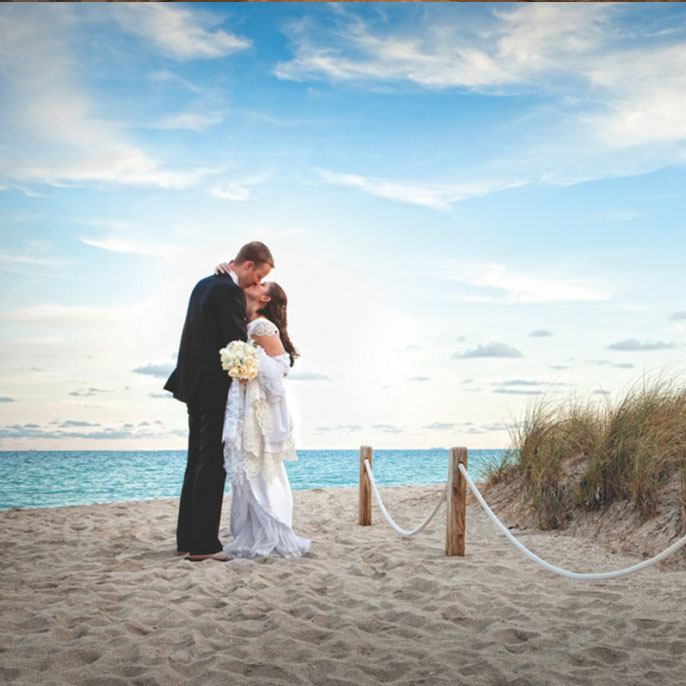 Groom and Bride kissing at the beach after the wedding